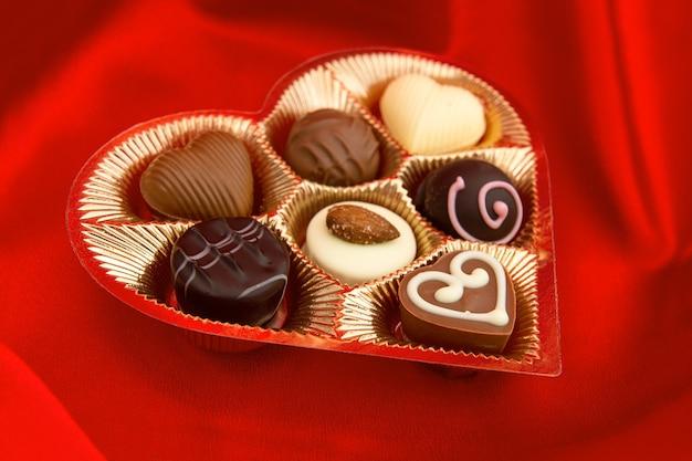 Bombons de chocolate em caixa de forma de coração de ouro sobre fundo de seda vermelho. foco seletivo