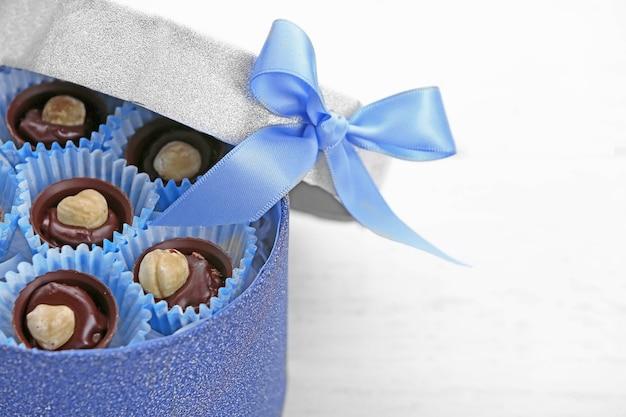 Bombons de chocolate em caixa de presente com laço em madeira clara