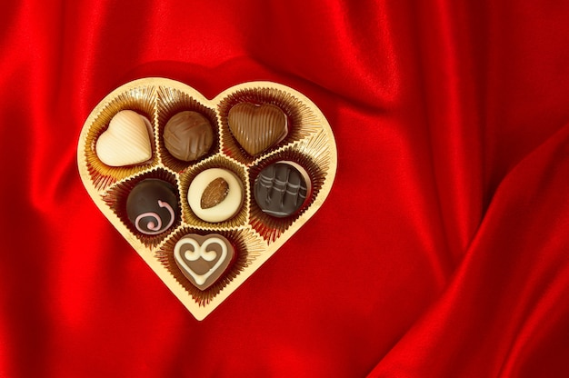 Bombons de chocolate em caixa em formato de coração de ouro sobre fundo de seda vermelha
