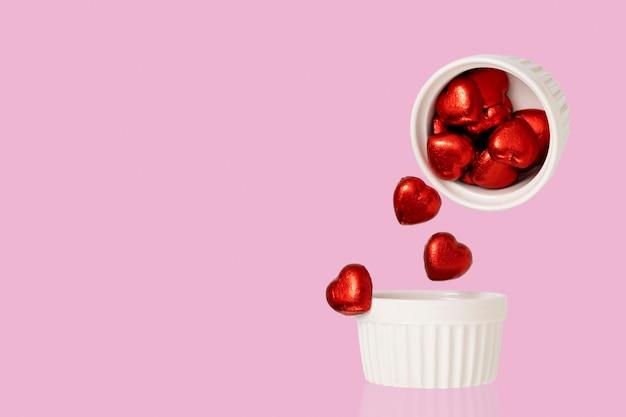 Bombons de chocolate em forma de coração caindo de uma xícara de cerâmica. fotografia de levitação de alimentos.
