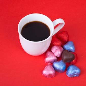 Bombons de chocolate em forma de coração com uma xícara de café