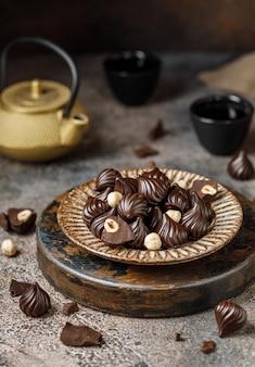 Bombons de chocolate em fundo marrom os pedaços de chocolate quebrado