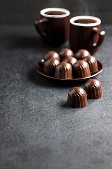 Bombons de chocolate em um prato e duas xícaras de café quente em um fundo preto com espaço de cópia