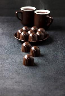 Bombons de chocolate em um prato e duas xícaras de café quente no escuro com espaço de cópia