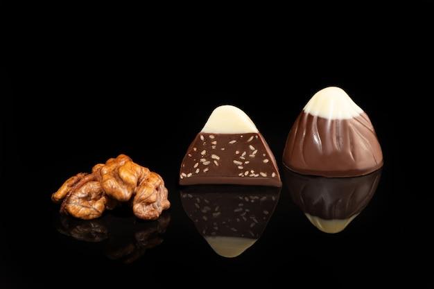 Bombons de chocolate em uma superfície escura com reflexo. recheio de nozes e frutas. copie o espaço.