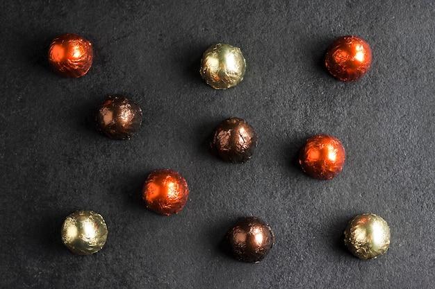 Bombons de chocolate embrulhados em papel alumínio multicolorido em fundo escuro. camada plana, vista superior