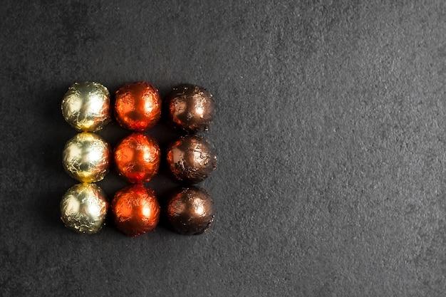 Bombons de chocolate embrulhados em papel alumínio multicolorido sobre fundo preto em forma de quadrado, com espaço de cópia. camada plana, vista superior