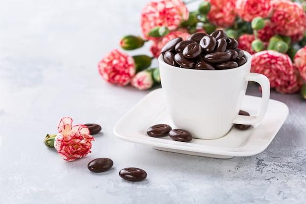 Bombons de chocolate escuro em copo de café branco