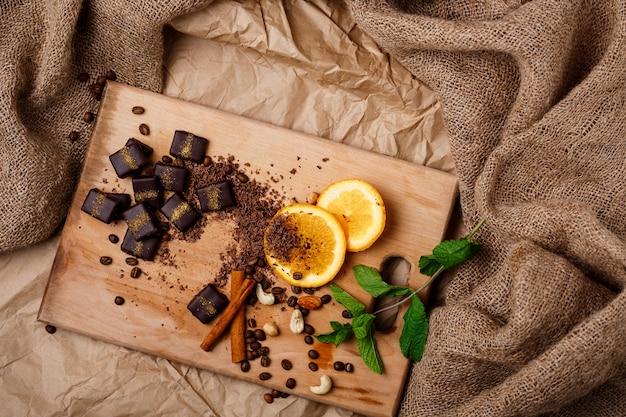 Bombons de chocolate laranja hortelã canela e nozes na mesa de madeira.