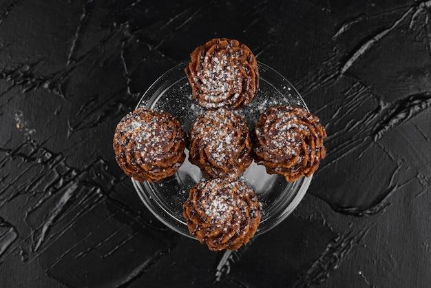 Bombons de chocolate na superfície preta.