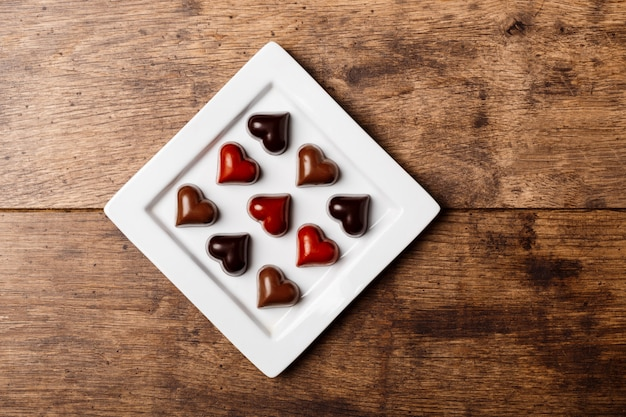 Bombons de chocolate no prato branco na madeira