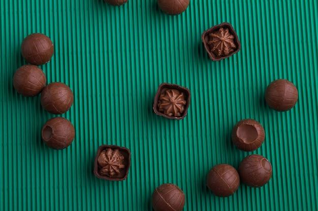 Bombons de chocolate praliné marrom de vista superior sobre fundo verde. doces doces redondos de chocolate.