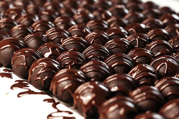 Bombons de chocolate redondos. fundo escuro, sobremesa de luxo, chocolate escuro, feito à mão.