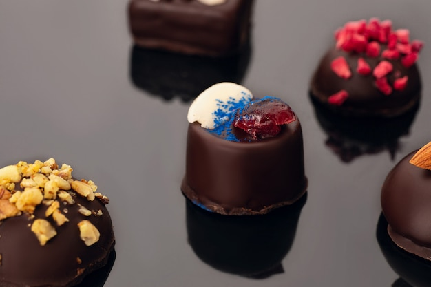 Bombons de chocolate sem açúcar em acrílico preto.