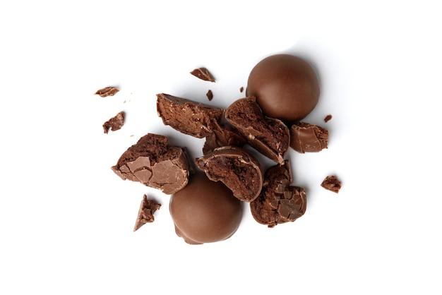 Bombons de praliné de chocolate quebrados isolados no fundo branco.