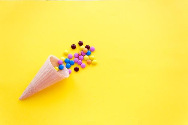 Bombons pequenos coloridos, sobre fundo amarelo