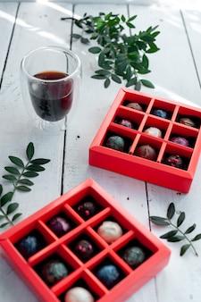 Bombons sortidos de trufas de chocolate artesanais em caixa com fundo de pedra branca