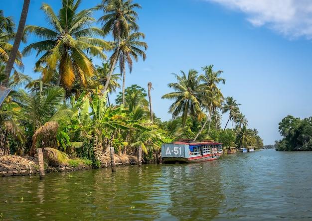 Bonde do rio no rio ao lado das palmeiras de alleppey, kerala índia.