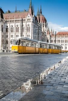 Bonde histórico passando pelo edifício do parlamento em budapeste