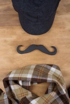 Boné, bigode preto e cachecol xadrez