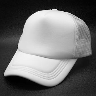 Boné branco sobre fundo escuro. chapéu de moda para o projeto.