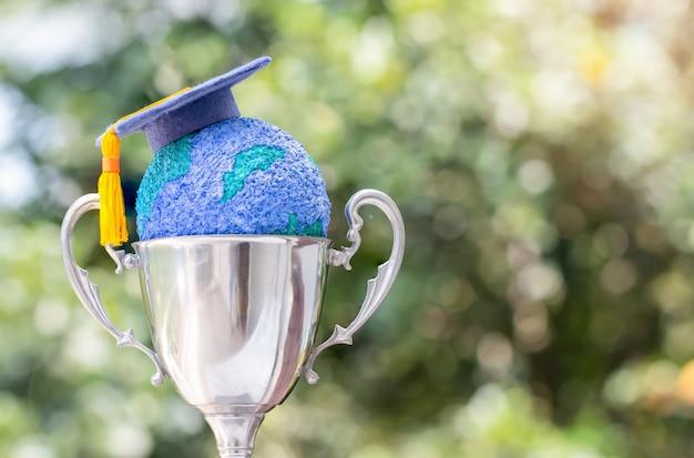 Boné de campeão do vencedor em educação na taça de troféu de prata para a competição de premiação com fundo verde claro