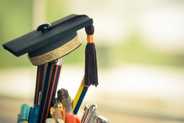 Boné de formatura coloque no lápis de cor na cesta. conceitual para a educação é o estudo de sucesso