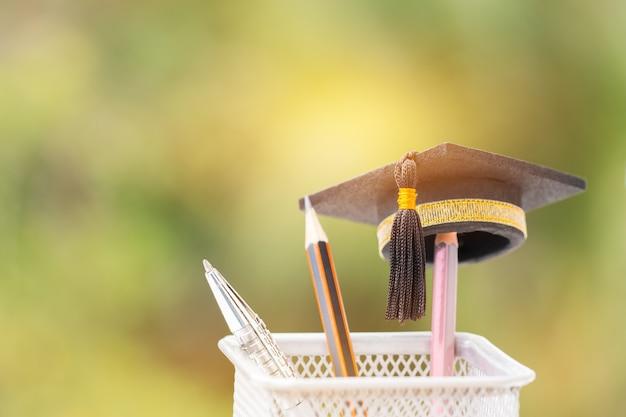 Boné de formatura coloque no lápis de cor na cesta conceitual para estudo de sucessos educacionais