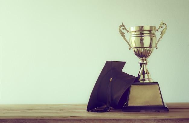 Boné de formatura com troféu de ouro campeão na mesa de madeira com espaço de cópia