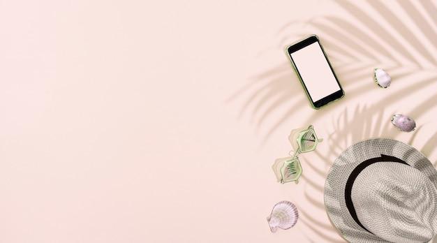 Boné de verão com acessórios pessoais em fundo rosa, com sombra em folha de palmeira