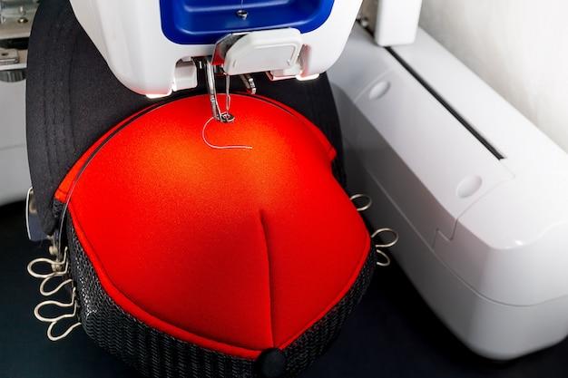 Boné vermelho na máquina de bordar de og de argola close-up imagens