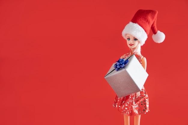 Boneca barbie segurando um presente com espaço de cópia