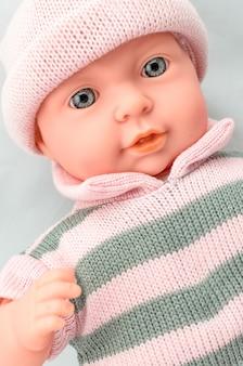 Boneca bebê fofo para menina em vestido de malha close-up