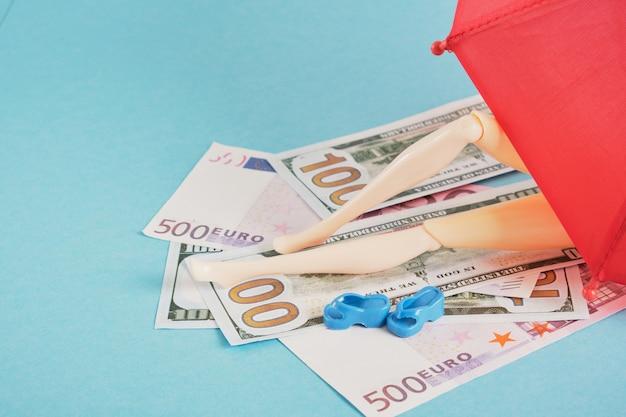 Boneca com dinheiro, como em toalhas de praia sob um guarda-chuva vermelho, espaço de cópia caro de conceito de férias na praia
