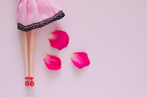 Boneca com pétalas de rosa cair da saia no fundo rosa. conceito de feromônio feminino de beleza mínima.