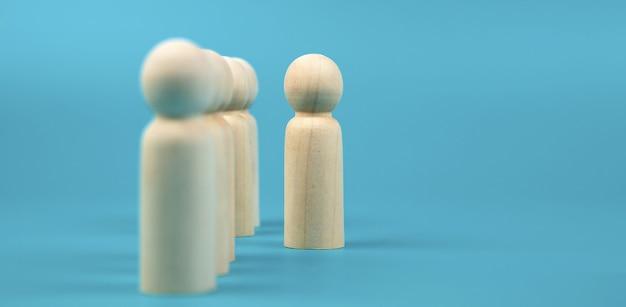 Boneca de madeira de pessoa em pé com muitos bonecos de madeira.