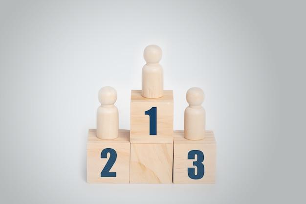 Boneca de madeira em pé no pódio 1, 2, 3 de blocos de construção de madeira, hierarquia de negócios, classificação.