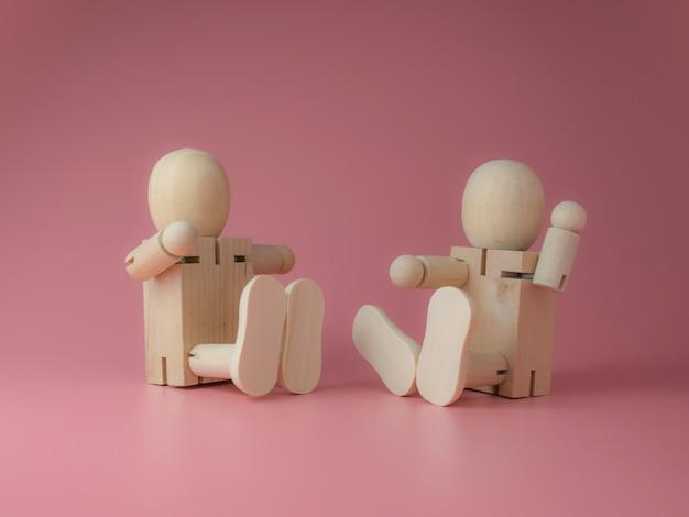 Boneca de madeira sentada e falando gestos em um fundo rosa.