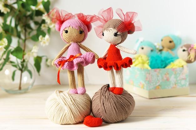 Boneca de malha artesanal em uma mesa de madeira. brinquedos em fio de lã.