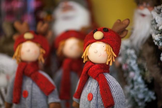 Boneca de natal com lenços e roupas de tricô e chapéu com chifres de rena