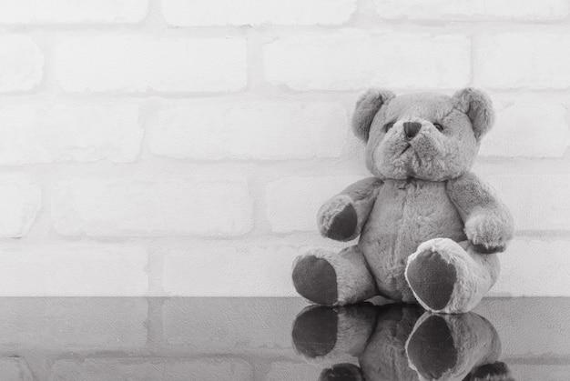 Boneca de urso bonito closeup na mesa de vidro preto e parede de tijolo branco