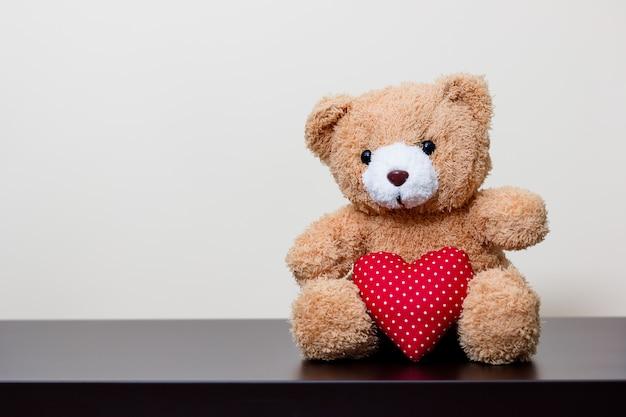Boneca de urso e coração vermelho na mesa de madeira