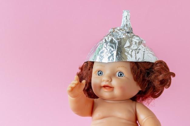 Boneca em um chapéu de folha de estanho, feito de folhas de papel alumínio