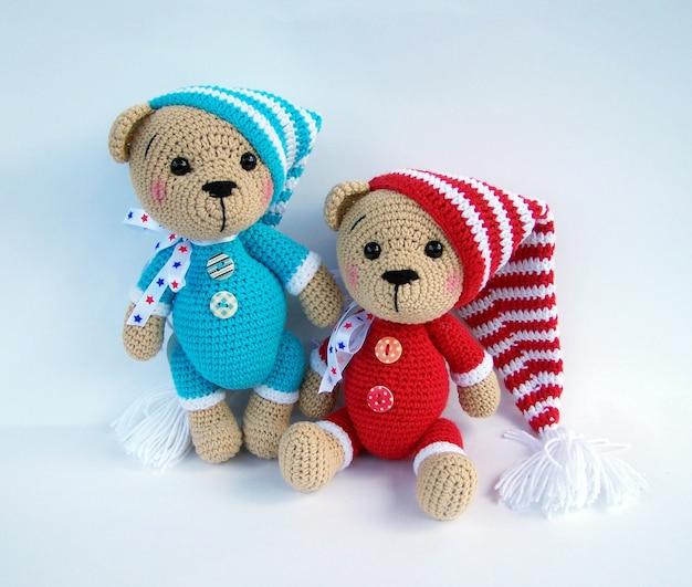 Boneca feito a mão bonito do urso do crochet isolada no fundo branco com reflexão da sombra.