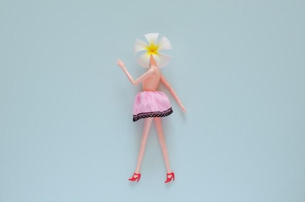 Boneca feminina nua em cima posando com flor de frangipani. mínimo conceito de beleza e moda.