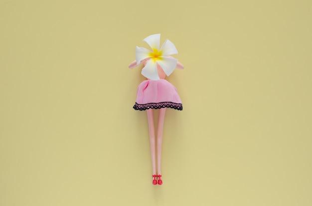 Boneca feminina nua em cima segurando flor frangipani. mínimo conceito de beleza e moda.