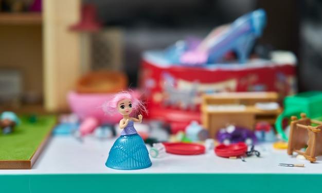 Boneca menina na mesa no borrão brinquedos quebrados
