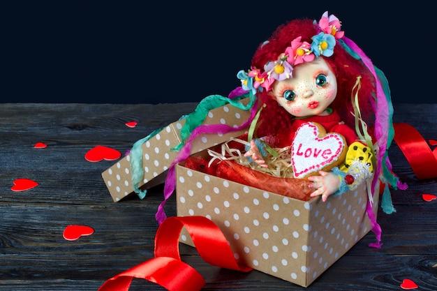 Boneca sentada em uma caixa de presente com um coração. nas mãos de um biscoito