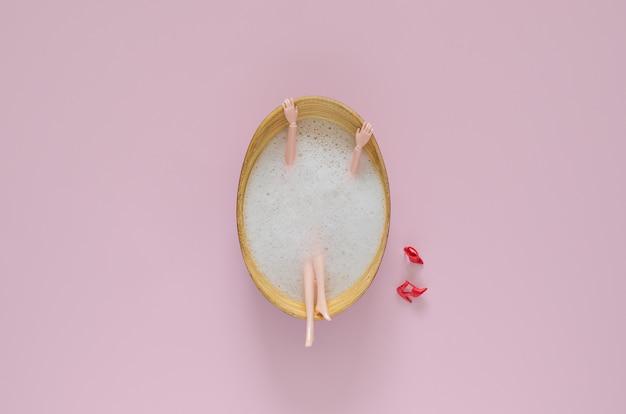 Boneca tomando banho com bolha na banheira de madeira no fundo rosa. conceito de verão beleza mínima vista superior.