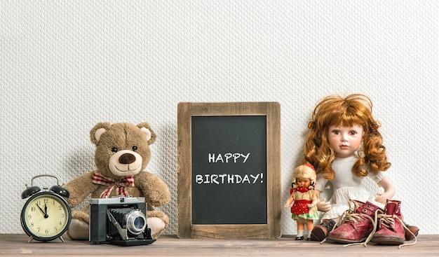 Boneca, ursinho de pelúcia, quadro-negro e brinquedos antigos. estilo retro ainda vida. texto de exemplo feliz aniversário! sem brinquedos de nome